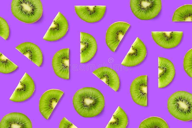 Fruit pattern of kiwi slices. Colorful fruit pattern of kiwi slices on purple background. Top view. Flat lay royalty free stock images
