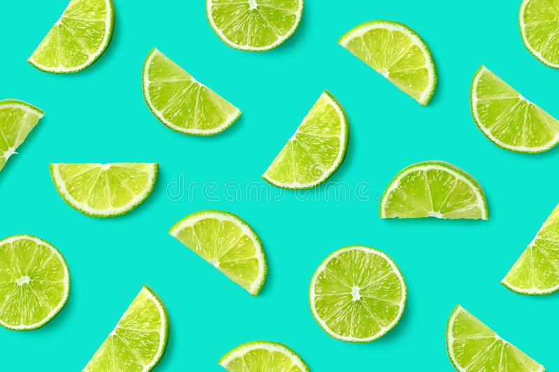 Fruit pattern of lime slices. Colorful fruit pattern of lime slices on blue background. Top view. Flat lay royalty free stock image
