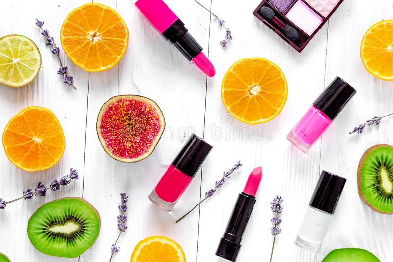 Fruit pattern with lipstick and nailpolish on white desk backgro. Citrus fruit pattern with kiwi, orange, lipstick and nailpolish on white wooden desk background royalty free stock image