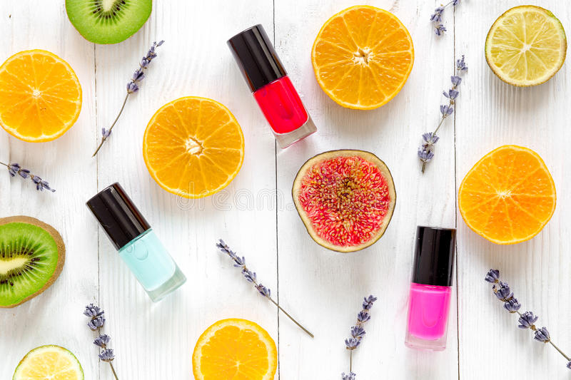 Fruit pattern with lipstick and nailpolish on white desk background top view royalty free stock photos