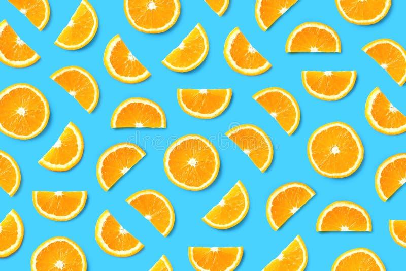 Fruit pattern of orange slices. Colorful fruit pattern of orange slices on blue background. Top view. Flat lay royalty free stock images