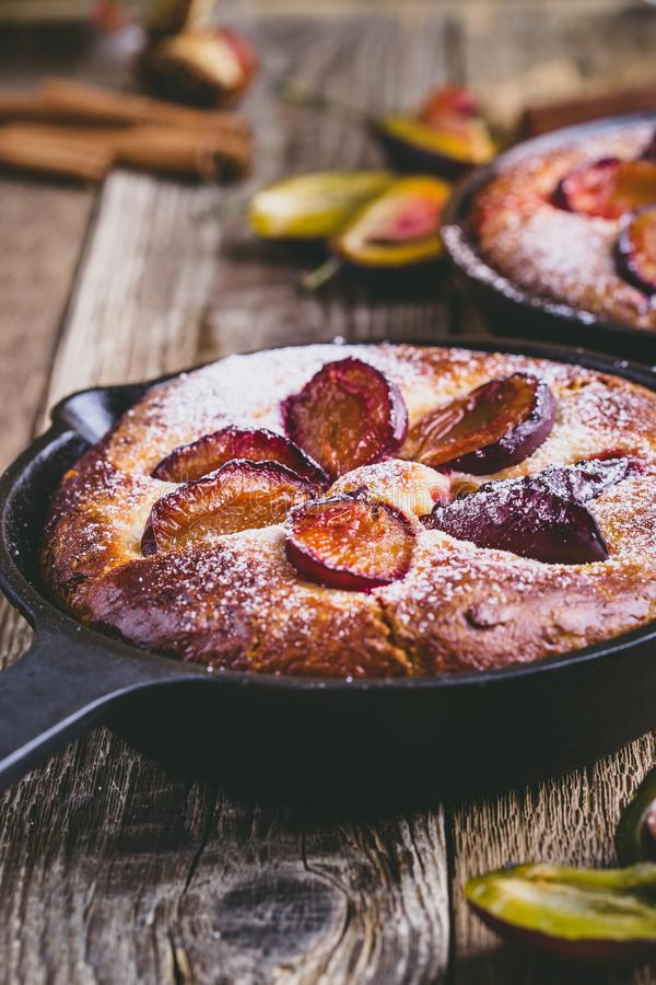 Fruit pie with fresh plums in cast iron skillet. Homemade fruit pie with fresh plums in cast iron skillet on rustic wooden table stock photo