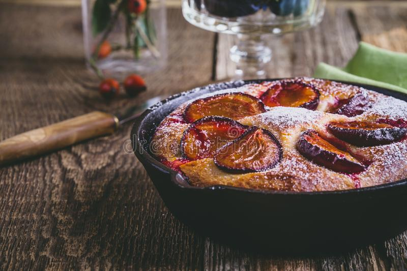 Fruit pie with fresh plums in cast iron skillet. Homemade fruit pie with fresh plums in cast iron skillet on rustic wooden table royalty free stock photos