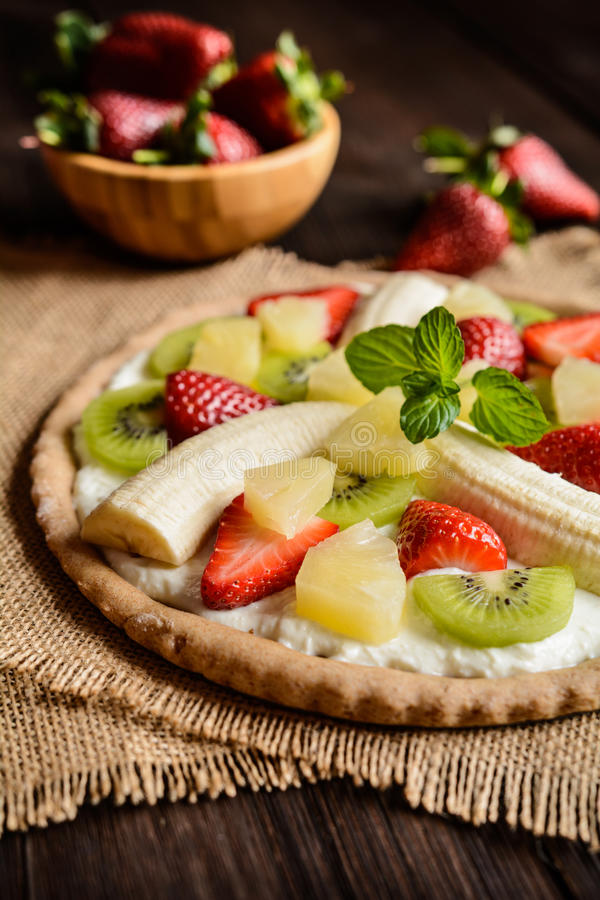 Fruit pizza with banana, kiwi, strawberry, pineapple royalty free stock images