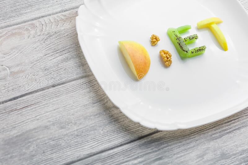 Fruit on a plate of of apple, kiwi, carrots, nuts. Fruit on a plate of a word diet of apple, kiwi, carrots, nuts and raisins. weight control for a healthy body royalty free stock photo
