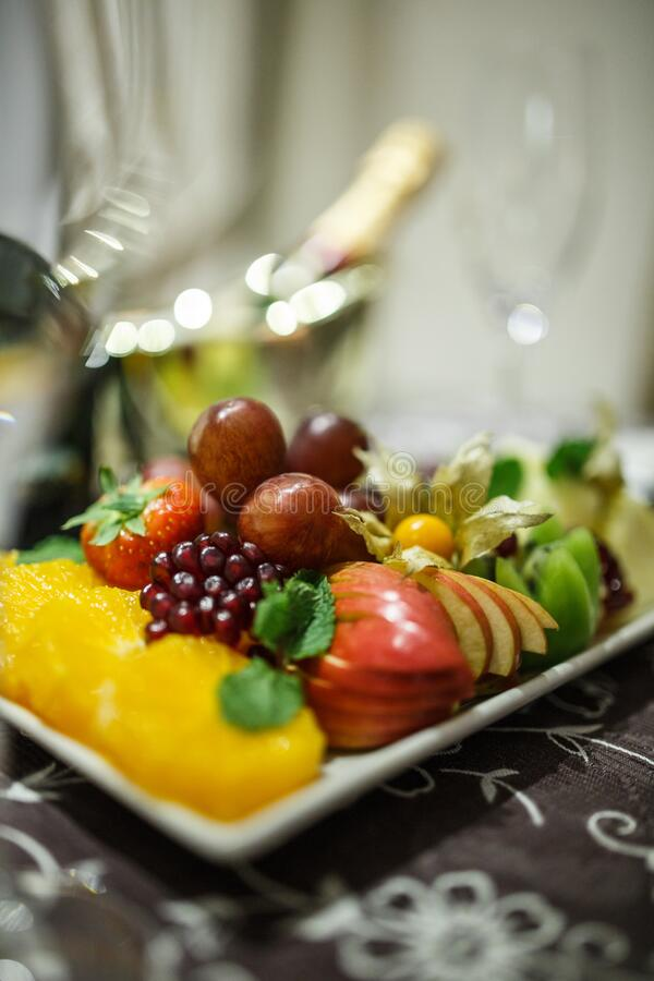 Fruit plate with apples, grapes, oranges, kiwis, strawberries. On the table royalty free stock photography
