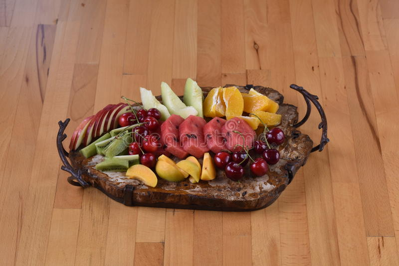 Fruit Plate. With water melon, apricot, cherry, apple orange, melon and kiwi served on a stone plate stock image