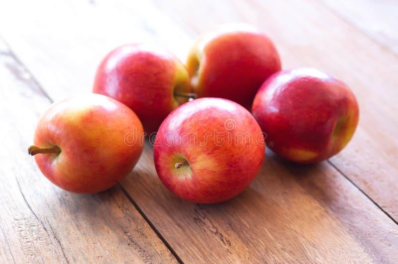 Fruit rouge frais de pommes de plan rapproché sur le fond en bois de table avec la lumière de la porte, concept d'alimentation sa photographie stock