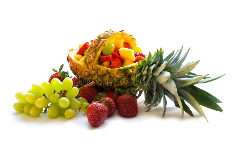 Fruit salad. A tropical fruit salad in a basket made of a pineapple. The salad is decorated with grapes and strawberries