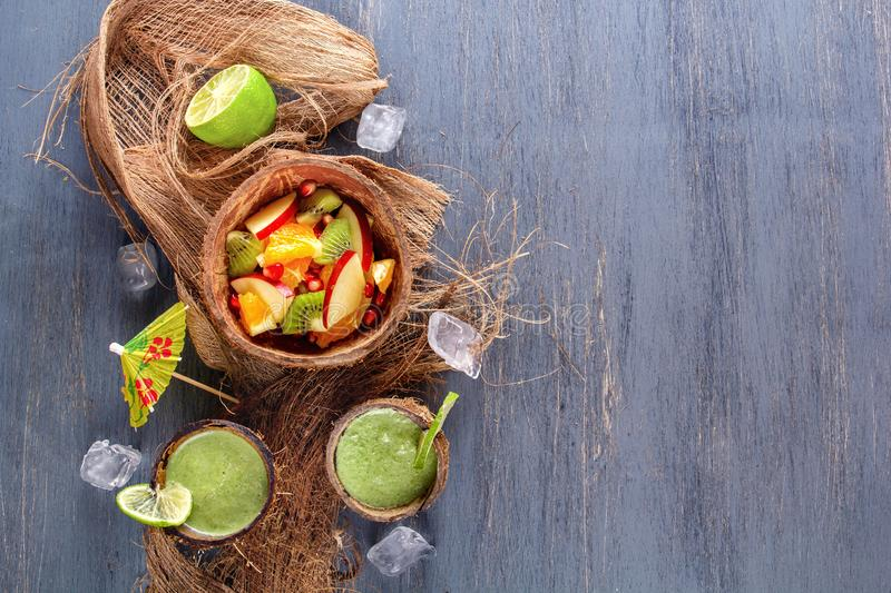 Fruit salad of apples, kiwi, orange and pomegranate in half of coconut with ice and fresh green smoothies with lime and mint. In coconut shell. Top view. The royalty free stock photos