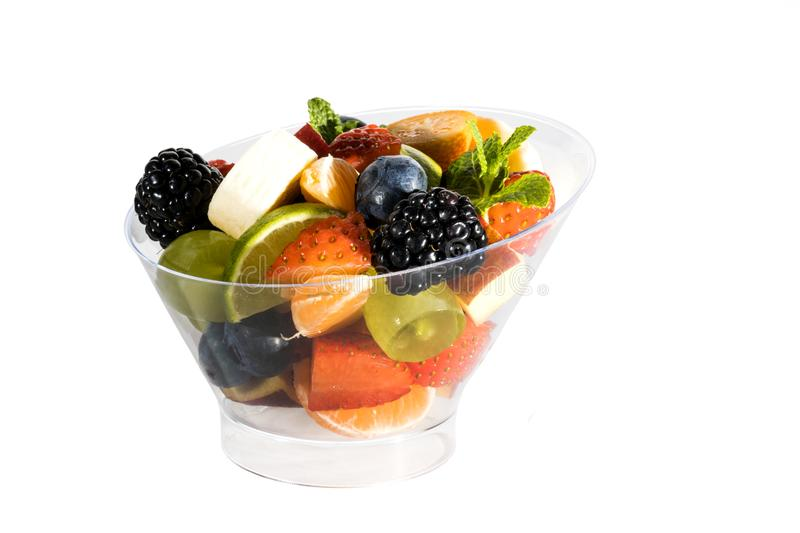 Fruit salad with bananas, strawberries, berries, in plastic utensils. On a white background stock photo