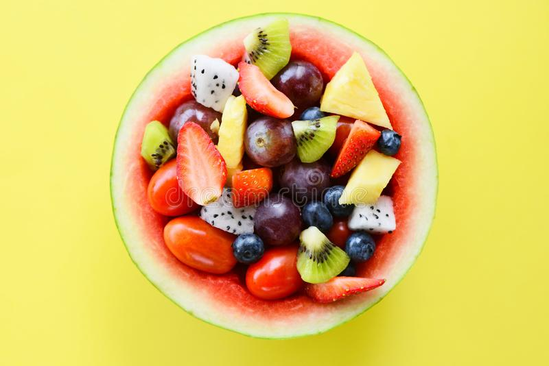 Fruit salad bowl served in a watermelon vegetables healthy food strawberries orange kiwi blueberries grape pineapple tomato lemon royalty free stock images