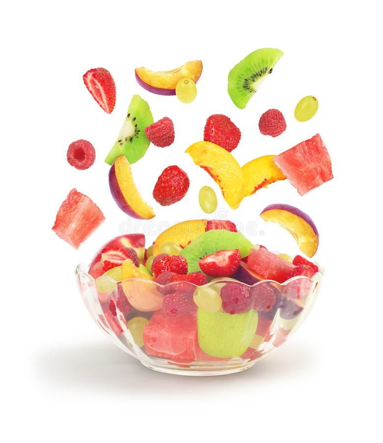 Fruit salad fall into glass bowl royalty free stock image