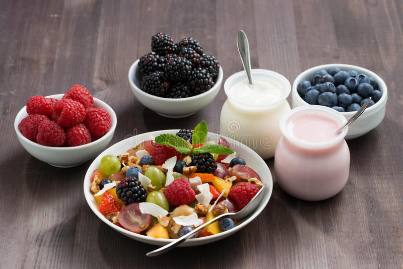 fruit salad, fresh berries and yoghurts on a wooden table royalty free stock images