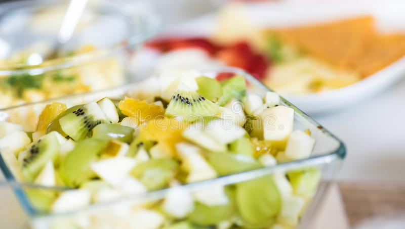 Fruit salad in glass bowl - healthy lunch idea - green grapes, banana, pear, kiwi fruit stock images