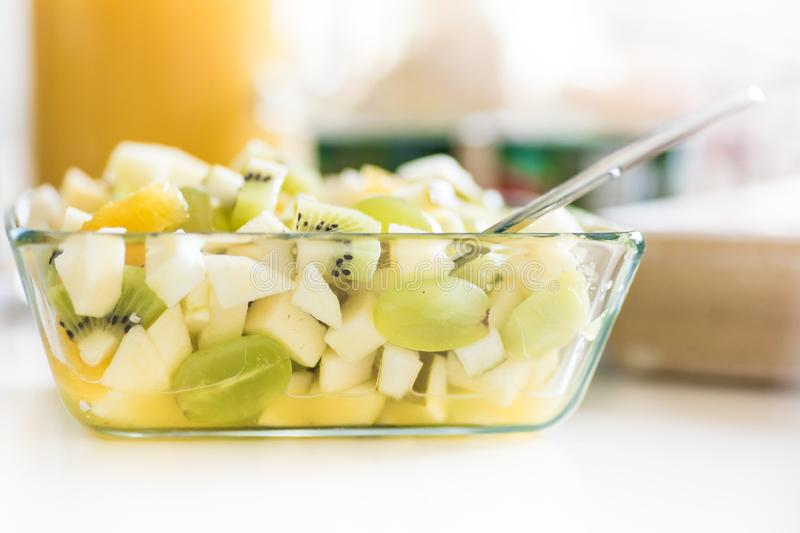 Fruit salad in glass bowl - healthy lunch idea - green grapes, banana, pear, kiwi fruit stock image