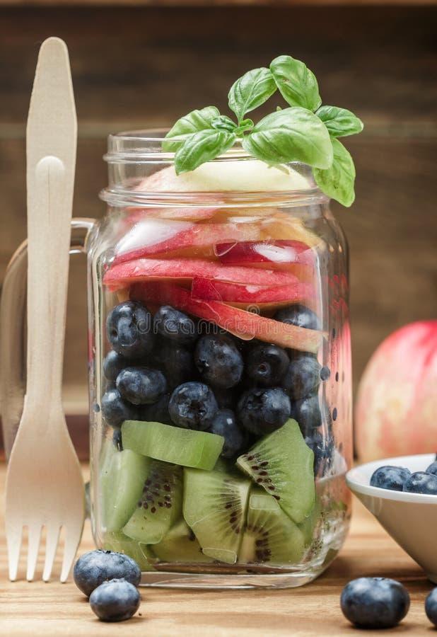 Fruit salad in a Mason jar. Kiwi, blueberry, peach, nectarine, mint, and Basil. Healthy Breakfast. detox. A rustic style. Selective focus royalty free stock photos