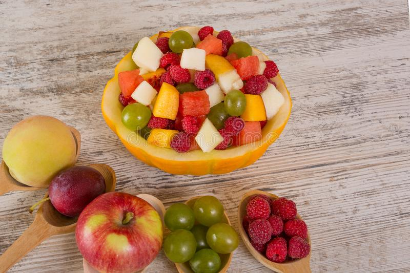 Fruit salad in melon and whole fruits in wooden spoons. Concept. Fruit salad. Peach, watermelon, melon, raspberry, plum, grapes, diced lie in a melon salad bowl stock photography