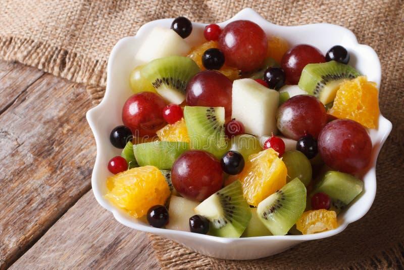 Fruit salad of oranges, grapes. pears, kiwis closeup. Horizontal royalty free stock photo