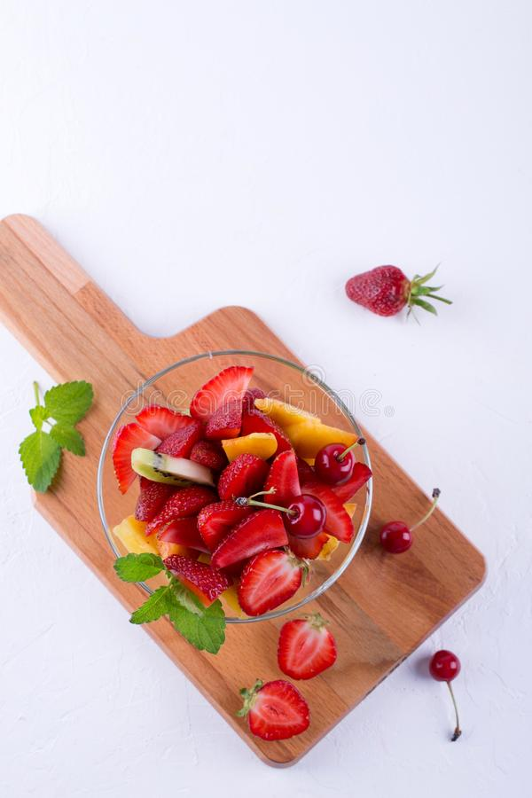 Fruit salad of strawberries, kiwis and apricots. Fresh and tasty snack Top view, place for text royalty free stock image