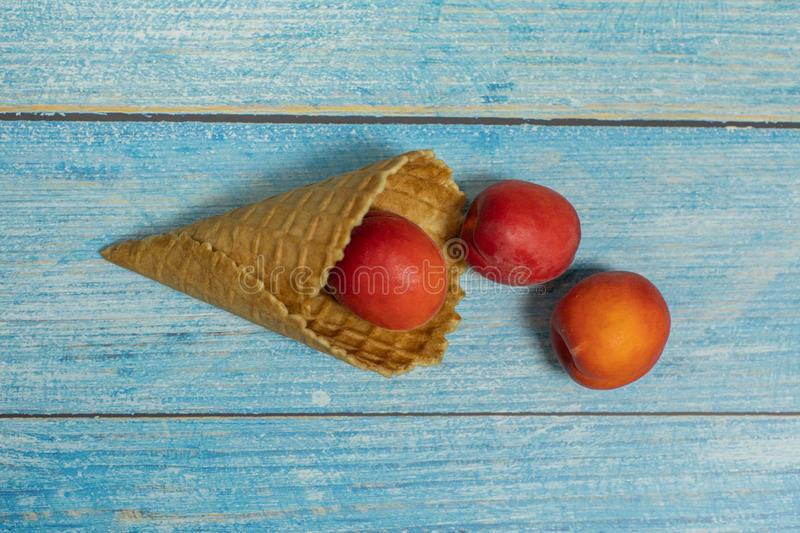 Fruit season. Fruit ice cream. Apricot in a waffle on a blue wooden background.  stock images