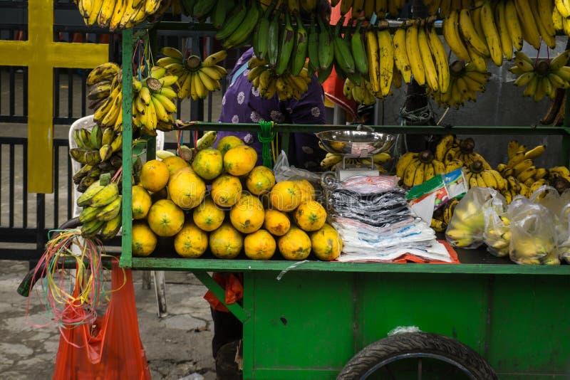 Fruit seller display various kind of exotic tropical fruit like banana and papaya on green cart photo taken in Depok royalty free stock photography