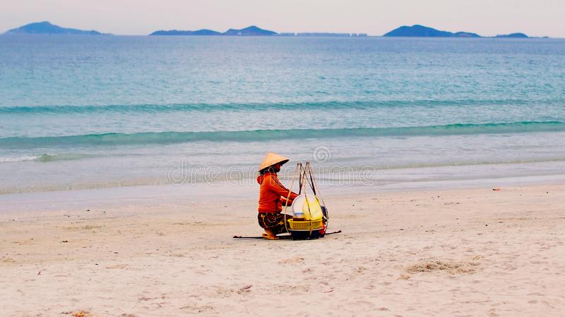Fruit seller in triangular straw hat On Vietnam Beach, Popular Tourist Destination, South Vietnam. Nha Trang, Asian with large baskets, selling food on the royalty free stock image