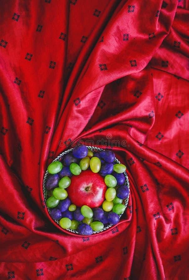 Fruit on silk fabric thank grapes Apple royalty free stock photo