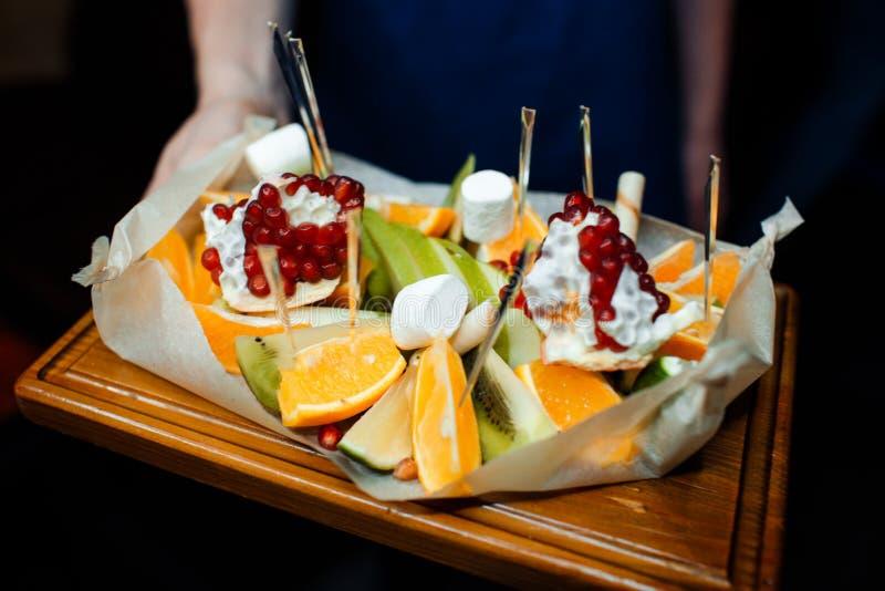 Fruit sliced pomegranate, orange and kiwi in a restaurant. royalty free stock image