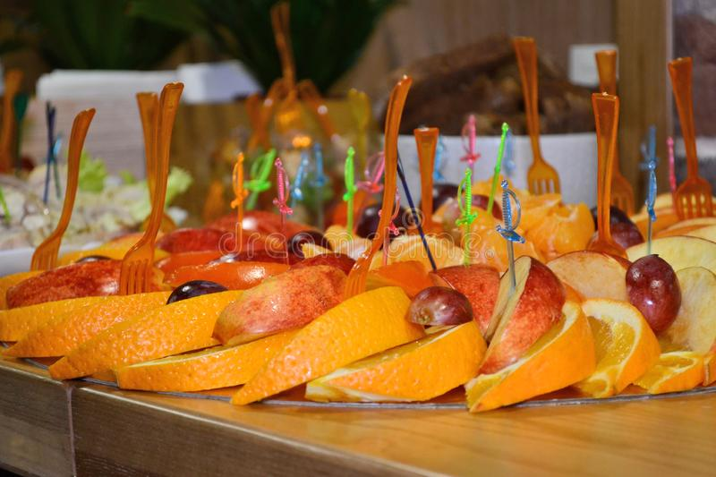 Fruit slicing of orange and apple with colorful plastic skewers on cocktail or a buffet table royalty free stock images