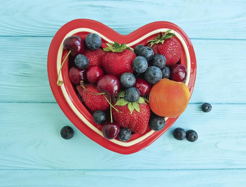 fruit strawberry, blueberry, cherry, apricot antioxidant detox plate heart on blue wooden stock photo