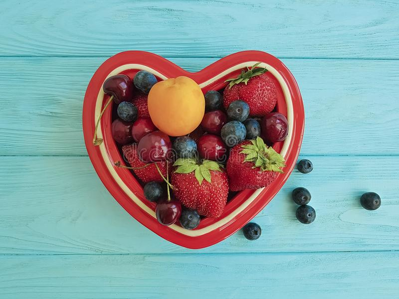 fruit strawberry, blueberry, cherry, apricot detox plate heart on blue wooden stock photography