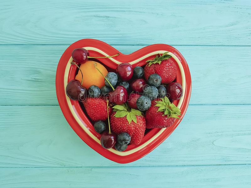 fruit strawberry, blueberry, cherry, apricot plate heart on blue wooden royalty free stock photo