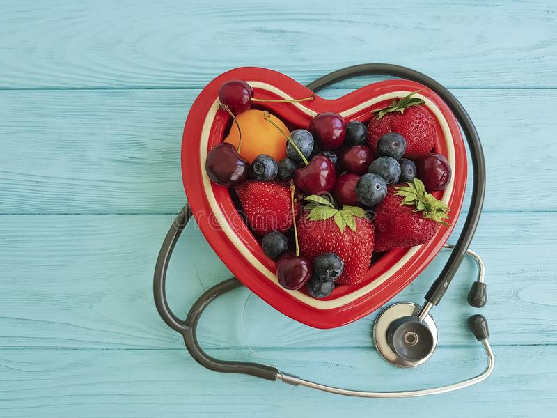 Fruit strawberry, blueberry, cherry, apricot plate heart on blue wooden stethoscope sweet antioxidant mixed stock photography