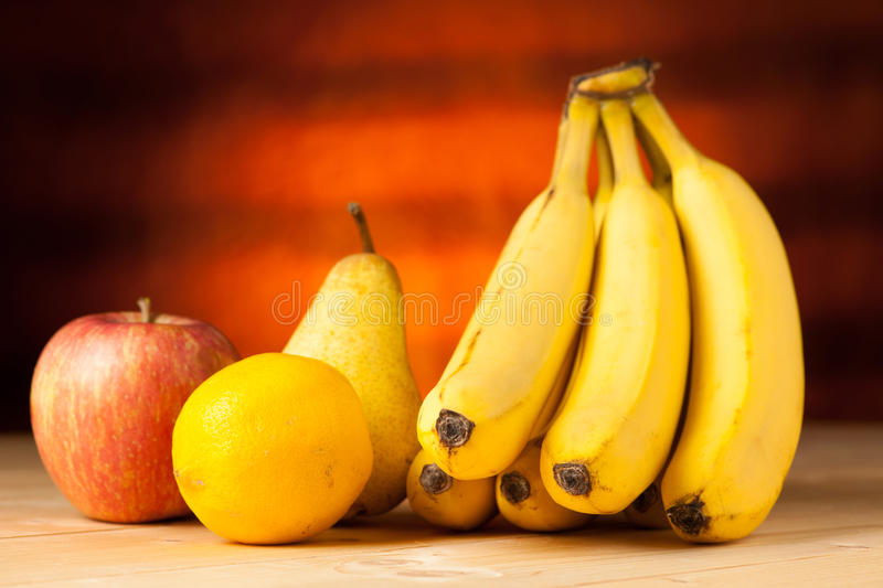 Fruit on the table - bananas pear apple and lemon wo a wooden de royalty free stock photos