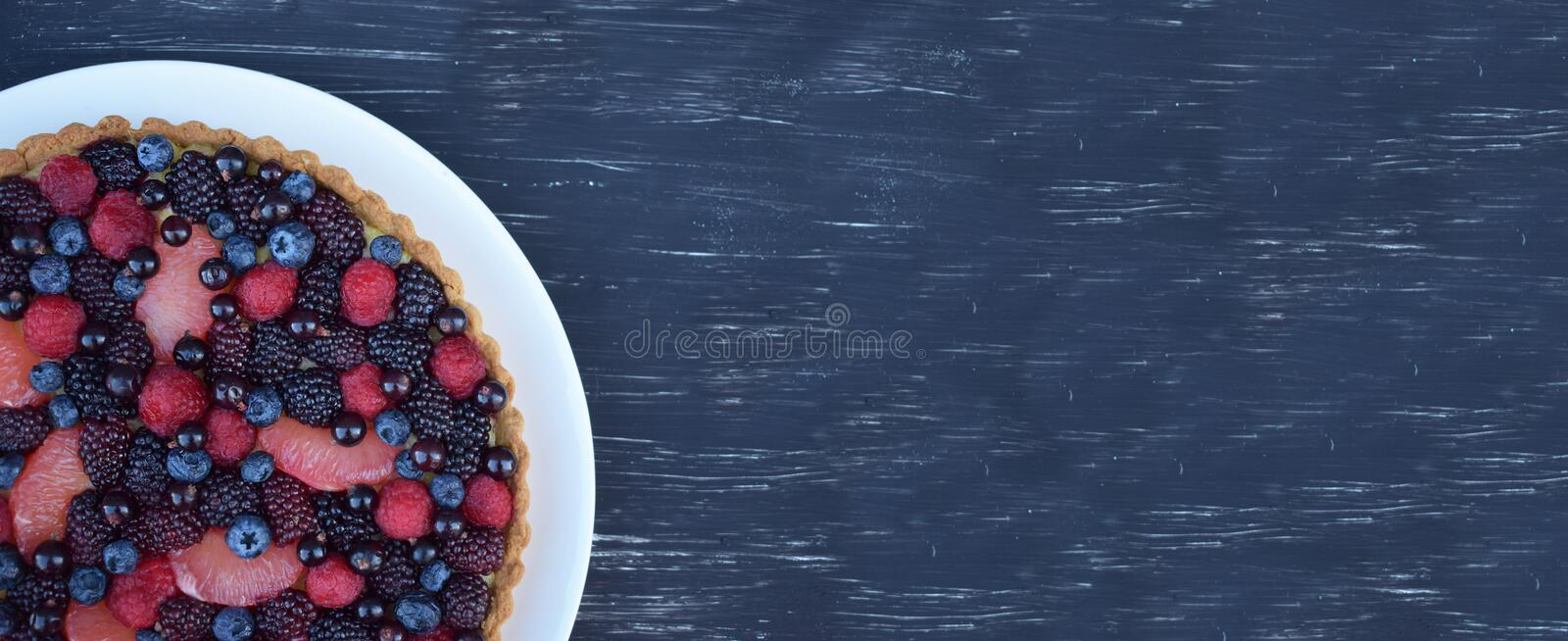 Fruit Tart Dessert Homebaked Fresh Raspberry Blueberry Grapefruit Summer Berries. Homemade Cake. Top view. Isoalted. Banner. Blue. Fruit Tart Dessert Homebaked stock photo
