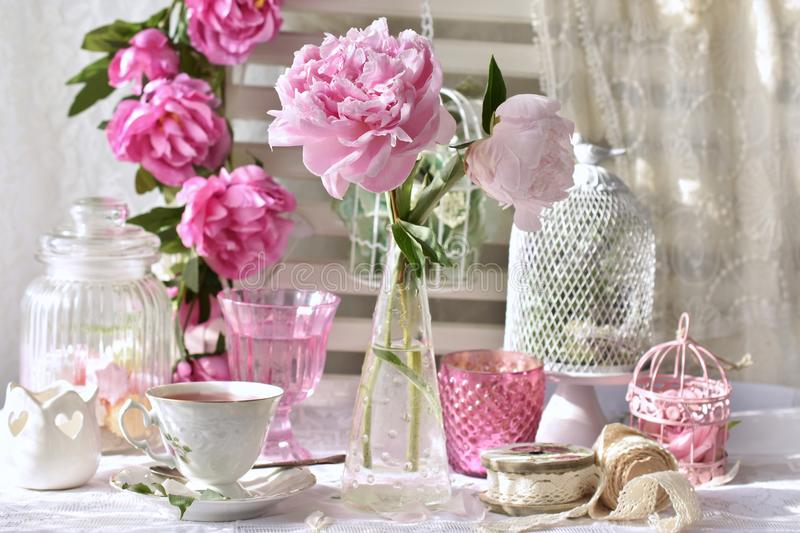 Fruit tea in beautiful porcelain cup and peony flowers. On the table in shabby chic style interior stock photography