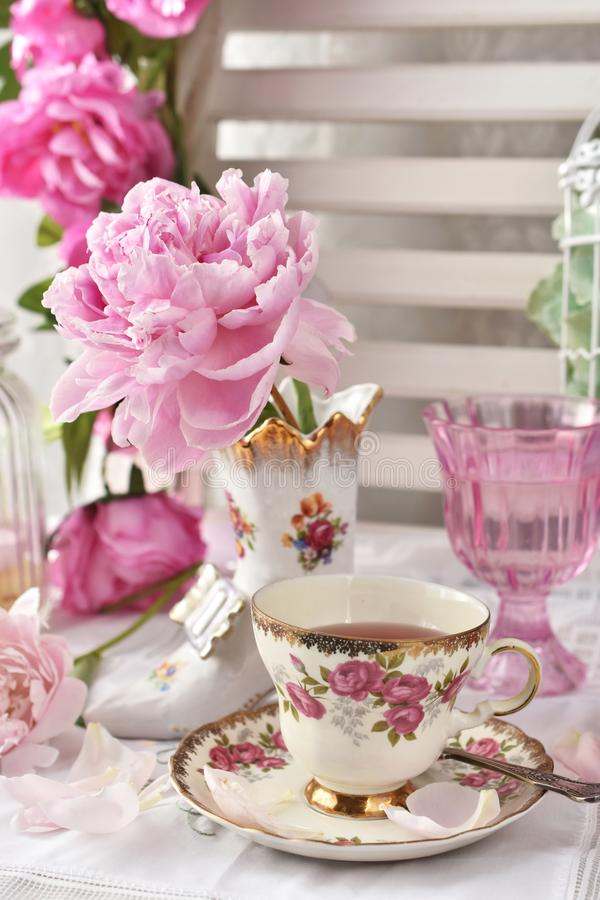 Fruit tea in beautiful vintage porcelain cup. And peony flower in shoe shaped vase royalty free stock photography