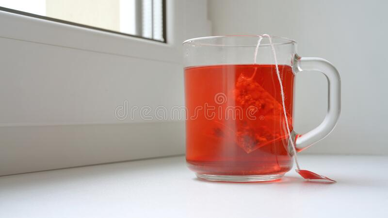 Fruit tea in glass cup with pyramid teabag. Red fruit tea in glass cup with pyramid teabag on windowsill breakfast concept royalty free stock images