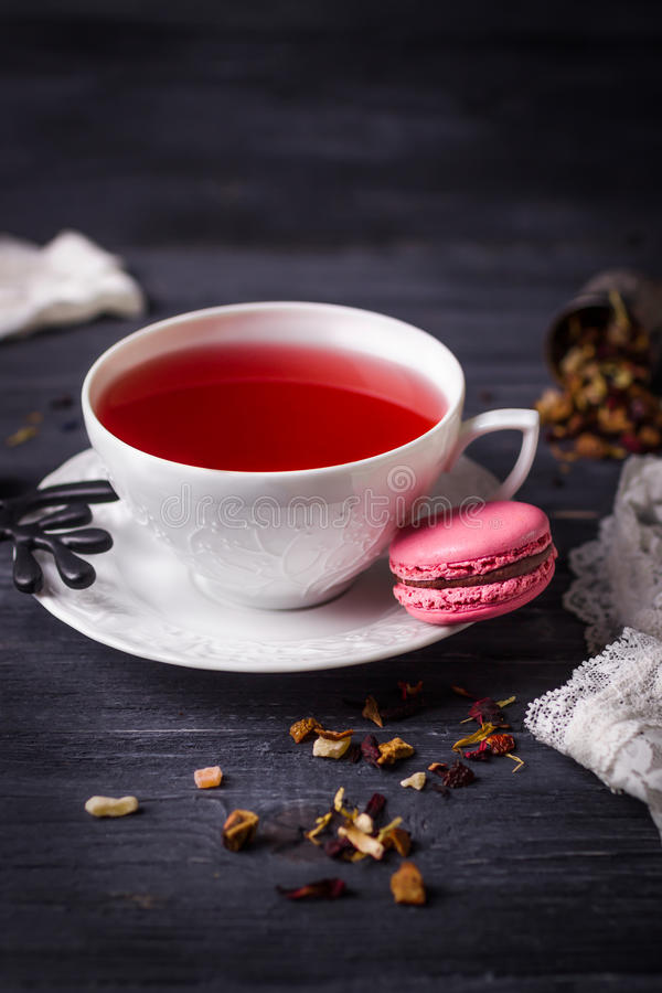 Fruit tea and pink raspberry macaron on black wooden background. Traditional French sweets royalty free stock photography