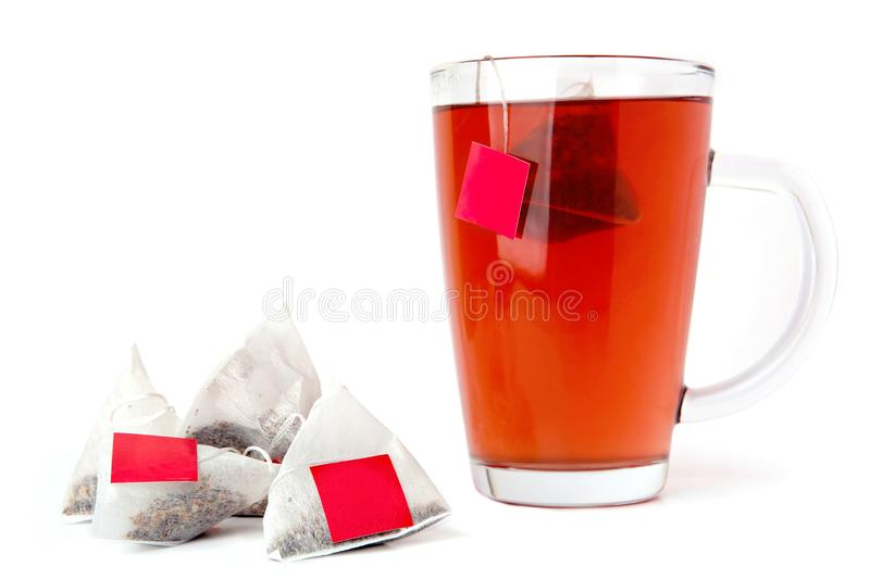 Red tea glass cup with tea bags isolated on white background. Fruit tea with triangle tea bags in cup royalty free stock photography