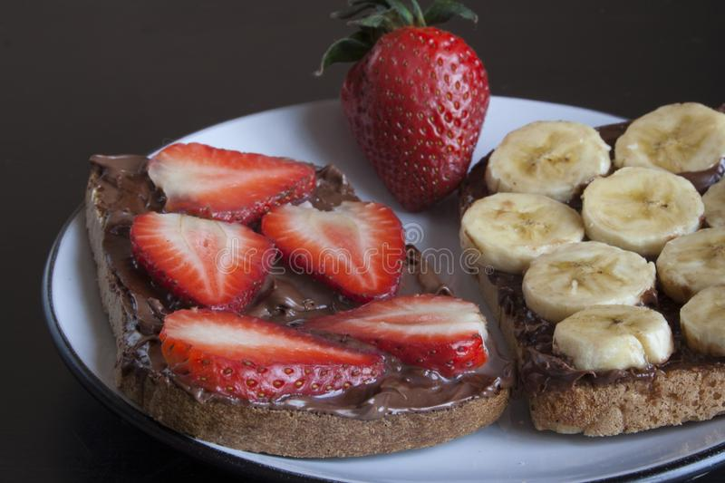 Fruit Toast with Chocolate Cream. Strawberry Banana Fruit Toast with Chocolate Cream and Whole Grain Bread royalty free stock image