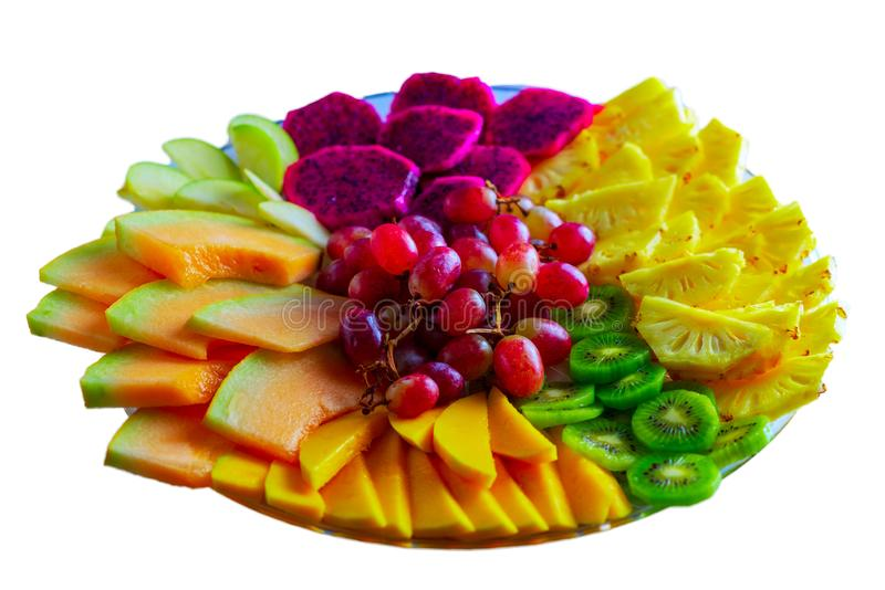 Fruit tray red pitaya dragon fruit, pineapple, grapes, mango, melon, kiwi on plate isolated on white background. royalty free stock image