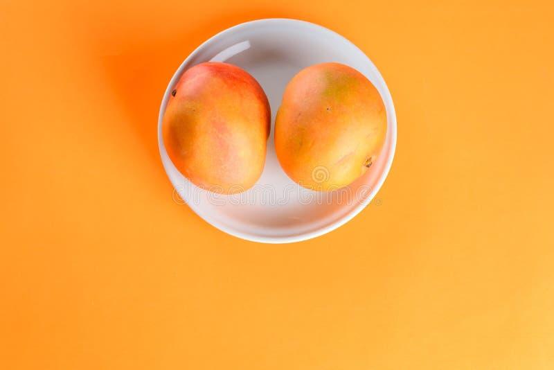 Fruit tropical de la mangue deux fraîche de plat sur le fond orange image libre de droits