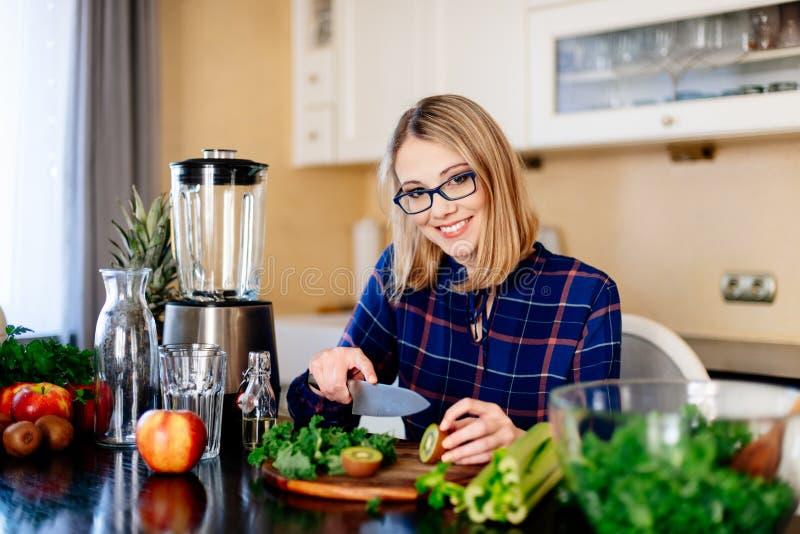 Fruit van de vrouwen het scherpe kiwi in keuken stock foto
