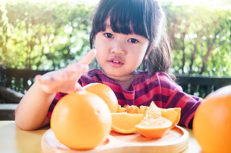 Fruit and Vegetable for Kids Concept. Little Cute 3-4 Years Old Girl with Sliced Orange on Wooden Plate. Fresh Juicy Fruit in Summer royalty free stock photos