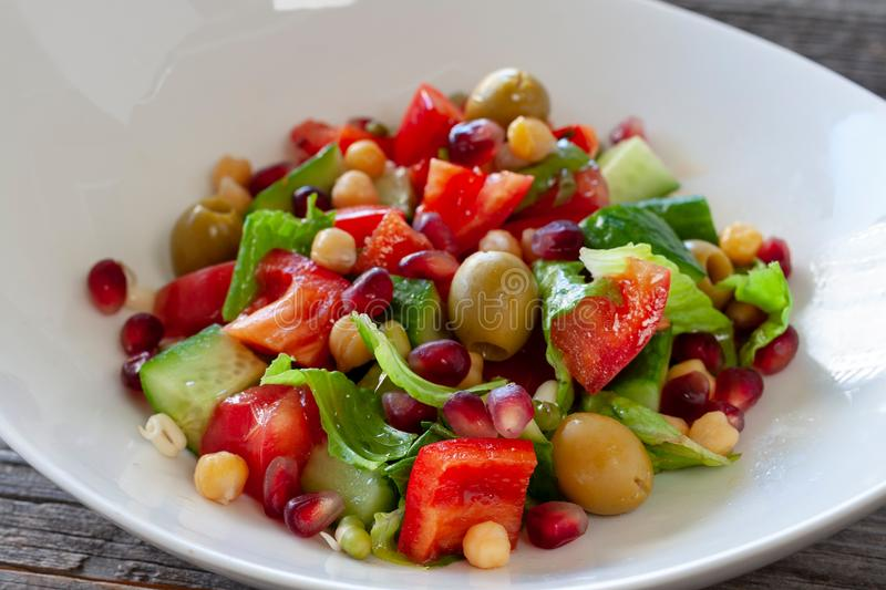 Fruit and vegetable salad: olives, pomegranate seeds, sweet peppers, corn, sprouted seeds and lettuce leaves. Vegetarian dish. Fruit and vegetable salad: olives royalty free stock photography