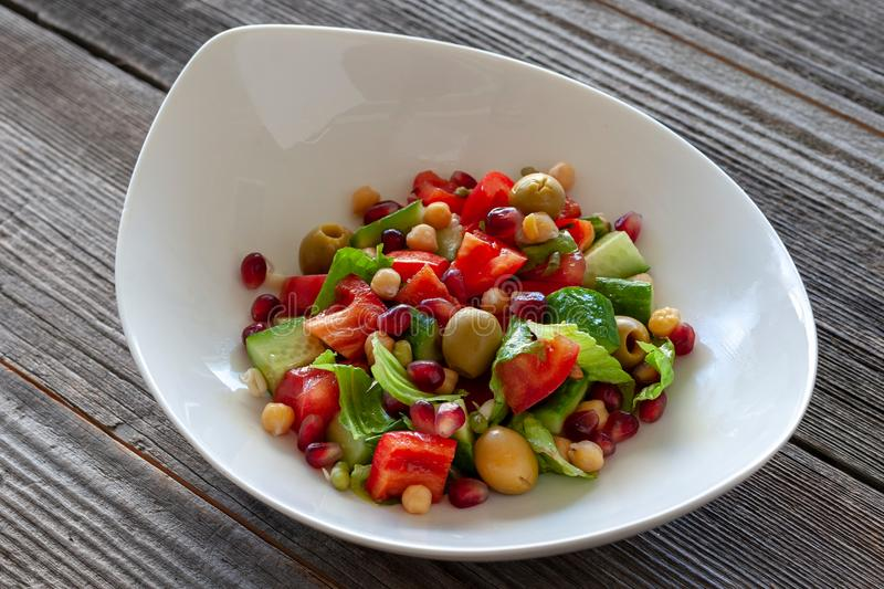 Fruit and vegetable salad: olives, pomegranate seeds, sweet peppers, corn, sprouted seeds and lettuce leaves. Vegetarian dish. Fruit and vegetable salad: olives royalty free stock image