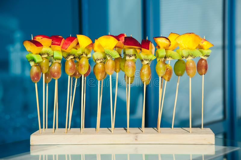 Fruit vegetarian canape at skewers with grapes, kiwi and peach at pure blue background. catering snack service stock photo