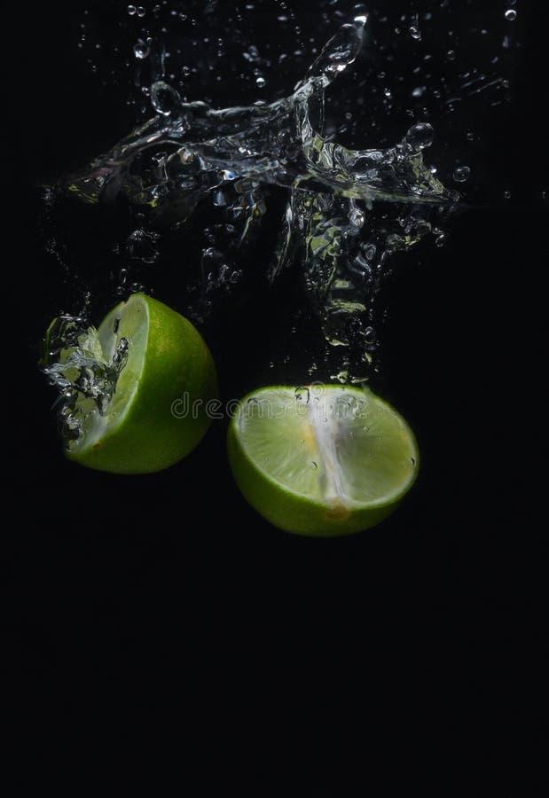 Fruit vert de chaux qui tombe et a l'eau ?cartant avec un fond noir photos libres de droits
